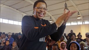 Graca Machel reacts as children sing happy birthday to Mr Mandela at a community centre in Qunu