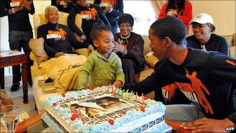 "A picture released by the Mandela Family shows South Africa""s iconic elder statesman Nelson Mandela (2ndL), dubbed Madiba, celebrating his birthday with his family in Qunu on July 18, 2011 as baby Zama Obiri cuts the cake with Mbuso Mandela"