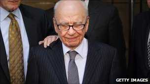 Rupert Murdoch looks down as he leaves a London hotel surrounded by his personal security team