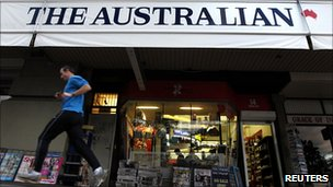 A man in Sydney runs past an advertising banner for The Australian newspaper which is published by News Limited