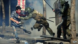 A student is arrested by riot police during a protest against the government of President Sebastian Pinera and a new education law, in Santiago on 14 July 14