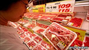 A woman examines beef in a supermarket