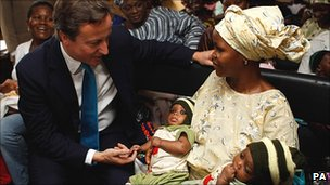 David Cameron chats to a mother of twins at a clinic in Lagos