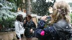 A woman takes a photo of two friends in fake snow at Latitude Festival 2011