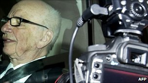 Photographers take pictures of News Corporation Chief Rupert Murdoch through his car window as he leaves his London home on July 14, 2011
