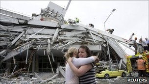 Two women hug each other in front of a collapsed building in central Christchurch February 22, 2011