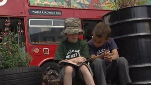 Kids reading outside their school library - which used to be a bus!