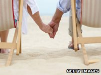 Couple holding hands sitting in deck chairs