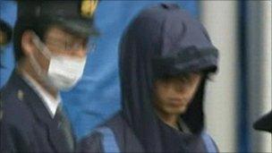Tatsuya Ichihashi (rt) led away by a policeman