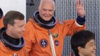 John Glenn waving and wearing his space gear