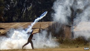 A protester throws back a teargas canister fired by police during an anti government demonstration in Lilongwe on July 20, 2011