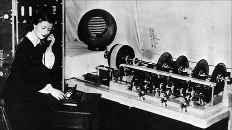 Ethel Jane Cain, first voice of the Speaking Clock in 1936, with the glass discs that carried the recordings she made 