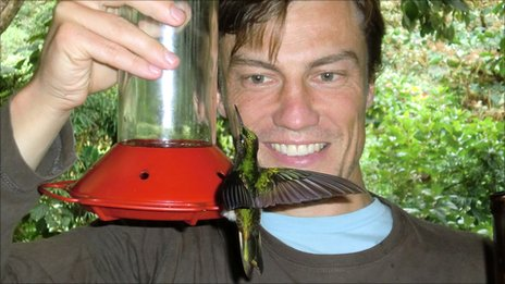 Peter Allison with a hummingbird on a feeder