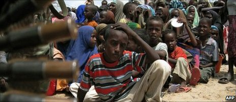 Somali displaced people wait for a food-aid distribution at a camp in southern Mogadishu on 21 July 2011