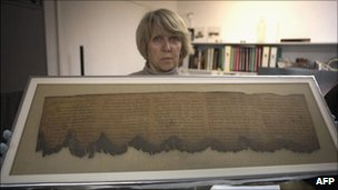 Conservationist holds up fragment of the Dead Sea Scrolls.