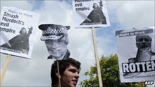 A protester in London, with placards of Rupert Murdoch and police