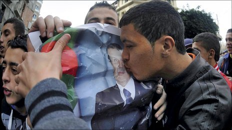 A man kissing a poster of Algeria&#039;s leader