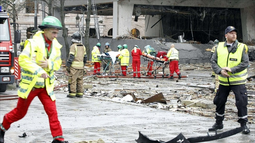 Firefighters evacuate two victims from a building hit by an explosion in Oslo, Norway, 22 July 2011