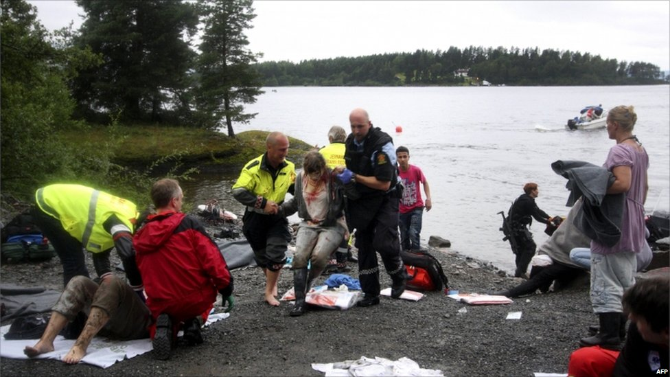 A wounded woman is brought ashore opposite Utoeya island (in the distance), having been rescued after a gunman who went on a killing rampage targeting a Norwegian Labour Party youth camp, 22 July 2011