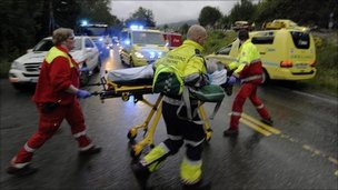 Rescue personnel take away an injured victim from a summer camp on the Norwegian island of Utoeya after a gunman opened fire on Friday night