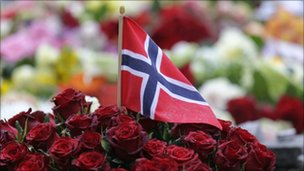 A Norwegian flag sticks out of a bunch of red roses placed on the market square outside the Oslo cathedral to mourn the victims of a bomb blast and a rampage