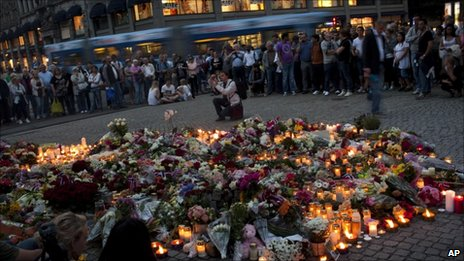 People gather at a candle-lit vigil near Domkirke, a cathedral in central Oslo, to pay tribute to victims of Friday's twin attacks, 23 July 2011