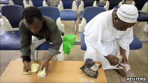 People count the old currency before receiving the new Sudanese currency at a branch of the central bank of Sudan in Khartoum
