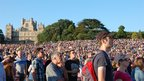 People in the crowd at Splendour with Wollaton Hall in the background