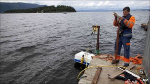 An emergency worker prepares a mini-submarine to search the water for victims killed on Utoeya island, seen in the background, 25 July