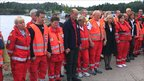 Norwegian Health Minister Anne-Grete Stroem-Eriksen, in black 6th right, and Sven Mollekleiv, head of the Norwegian Red Cross, in black 4th left, volunteers from the Red Cross and other organisations stand for a minute of silence at noon on Storoya island at midday