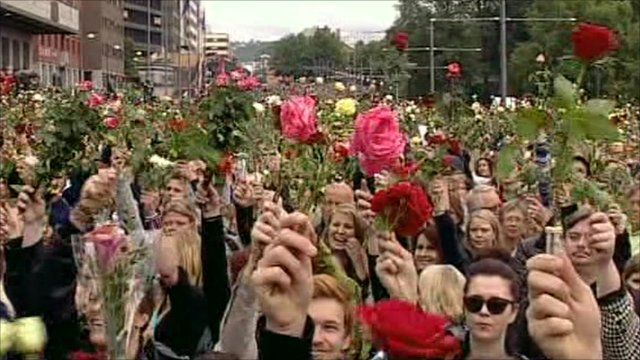 People in Oslo hold up roses