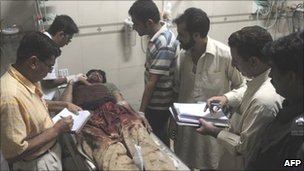 Paramedics treat an injured man in a Karachi hospital