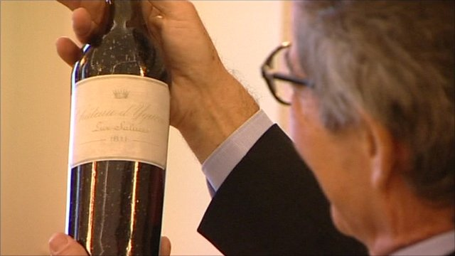 Collector holds up bottle of win bought for £75,000