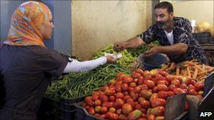 An Algerian market vendor sells vegetables to a woman in Algiers (Archive shot)