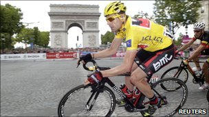 Cadel Evans of Australia, wearing the leader's yellow jersey, takes a curve in front of Paris' Arc de Triomphe during the final stage of the 98th Tour de France cycling race, 24 July 2011