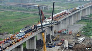 This photo taken on July 24, 2011 shows workers clearing wreckage of mangled carriages after a Chinese high-speed train derailed