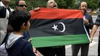 Protesters hold up the Libyan rebels' flag outside the embassy