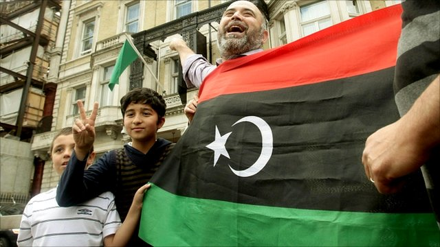 Protesters celebrate outside the Libyan Embassy in London