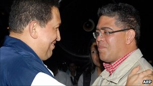 Venezuelan President Hugo Chavez (L) is welcomed by vice-president Elias Jaua Milano (R) on his arrival in Caracas after cancer surgery (4 July)