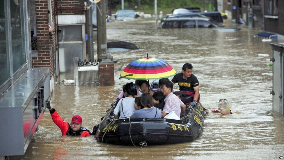 Rescue workers evacuate residents on a rubble boat from flooded area in Gwangju, South Korea