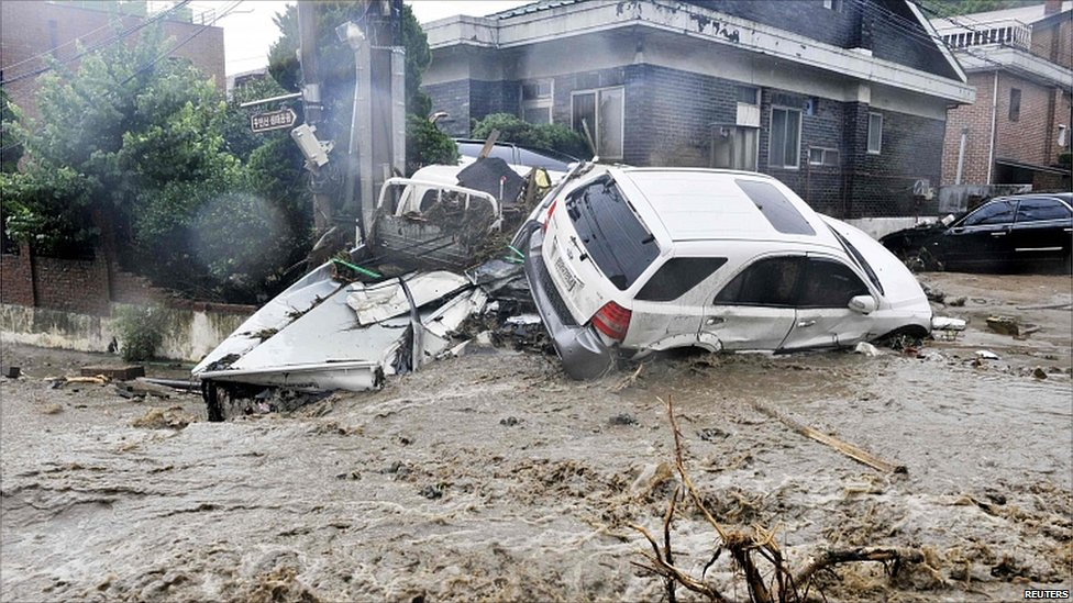 Damaged cars are seen after a landslide and heavy rainfall in Seoul.