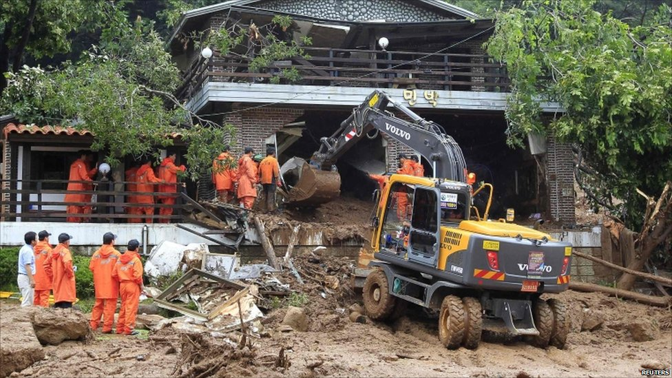 Rescue workers search for possible survivors among collapsed houses in Chuncheon, about 100km (60 miles) east of Seoul