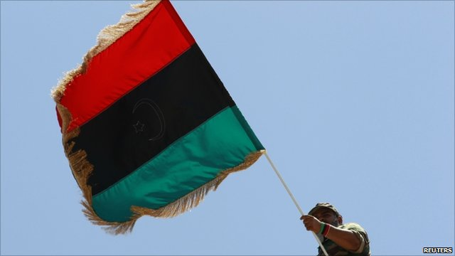 A rebel fighter waves a Kingdom of Libya flag