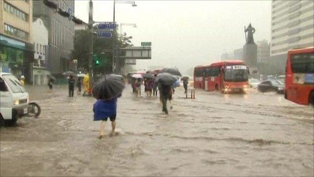 People walk on a flooded street