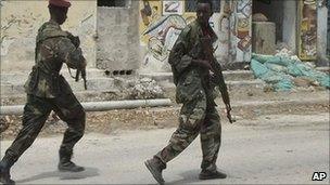 Somali government soldiers run to take up positions during clashes between Islamist insurgents and Somali government soldiers with (AU) peacekeeping forces in Mogadishu's southern Bakara market neighbourhood on Saturday 2 July 2011