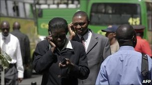 Kenyans chat on mobile phones in Nairobi (archive shot)