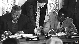 Joshua Nkomo (L) and Robert Mugabe (R) sign the Rhodesia ceasefire agreement at Lancaster House in London in 1979