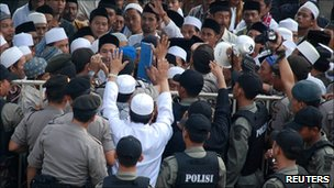 Indonesia police block Muslim supporters who are rallying in support of men accused of assault on members of the Ahmadiyah sect