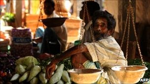 A Sri Lankan Tamil vendor looks from his stand in a vegetable market in Jaffna on 24  July 2011