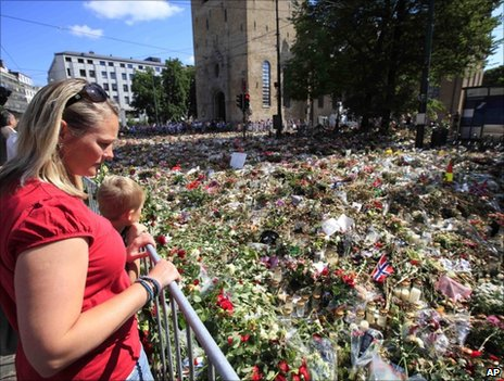 People look down from a balcony on flowers laid outside Oslo cathedral, 30 July